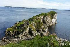 Ruinas do castelo de Kinbane (pedras brancas) e vista sobre Rathlin Island